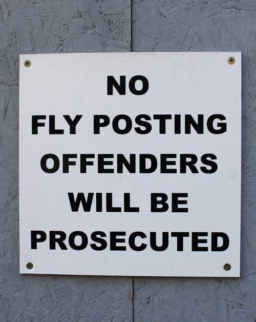 Photograph of sign on boards: No Fly Posting Offenders will be Prosecuted